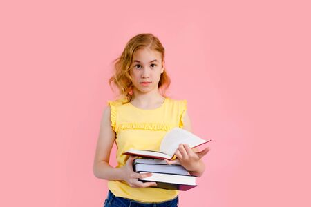 Photo of happy charming girl posing with exercise books and smiling isolated over pink background
