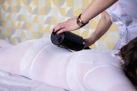 Lymphatic drainage massage LPG or R-sleek apparatus process. Woman in white suit getting anti cellulite massage in a beauty salon. Skin and body care.