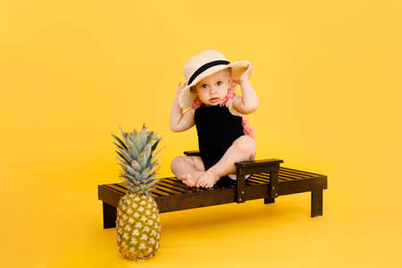 Funny little girl dressed in a red swimsuit, big hat and sunglasses heart sunbathes on a sun lounger.