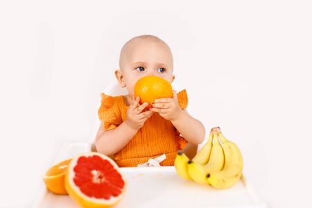 Infant girl sitting in high child's chair eating fruits on a white background. Baby food concept, space for text