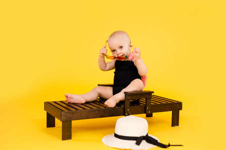 Funny little girl dressed in a red swimsuit, big hat and sunglasses heart sunbathes on a sun lounger. Reklamní fotografie