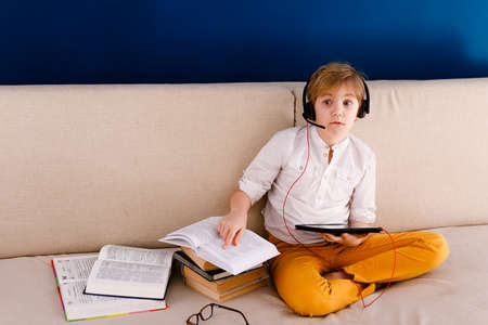 A boy with glasses and headphones is learning lessons with a tablet and books. Home distance learning online.