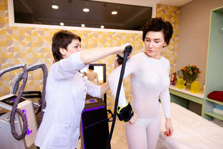 A female masseur gives an LPG massage to an attractive woman in a special white suit in a modern Spa.