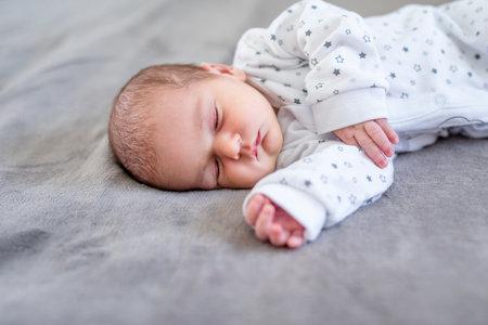 宝贝男孩睡觉第一天生活。和平地睡觉逗人喜爱的小新出生的孩子。