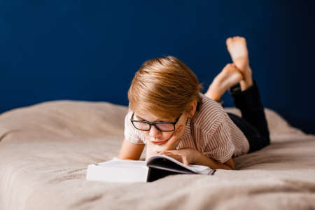 A 10-year-old boy with glasses is lying on the bed reading a big book. Banco de Imagens