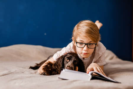 A 10-year-old boy with glasses and with his dog is lying on the bed reading a big book.
