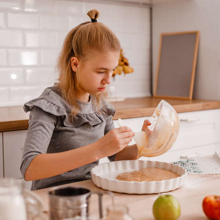 Attractive teenager girl is cooking on kitchen. Having fun while making cakes and cookies
