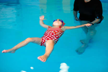 Cute baby girl in red swimsuit and special glasses playing in the pool.
