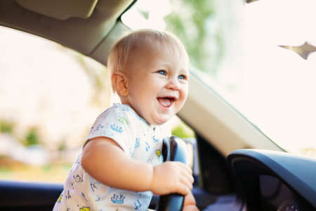 Cute little baby boy driving big car, holding steering wheel, smiling and looking forward with interest. Childhood game and dreams.