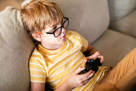 Blonde boy in big glasses playing on the console sitting on the couch. European child having a hobby.