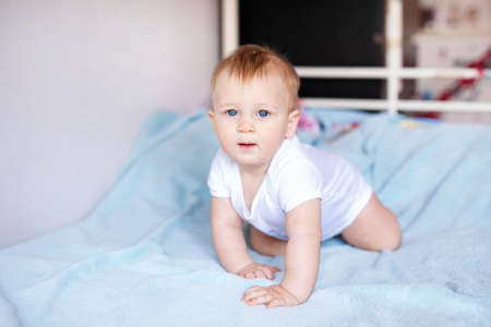 Adorable baby boy in white sunny bedroom. Newborn child relaxing on a blue bed. Nursery for young children. Newborn kid during tummy time with toys at a window.