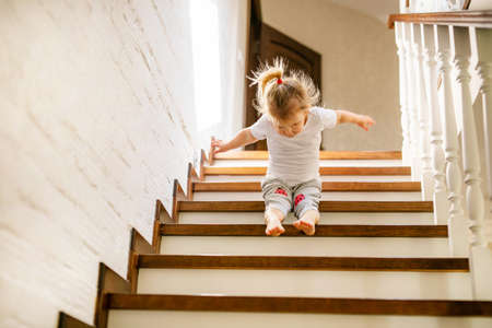 Baby blonde girl in white t-shirt at bottom of stairs indoors, looking at camera and smiling. Banco de Imagens