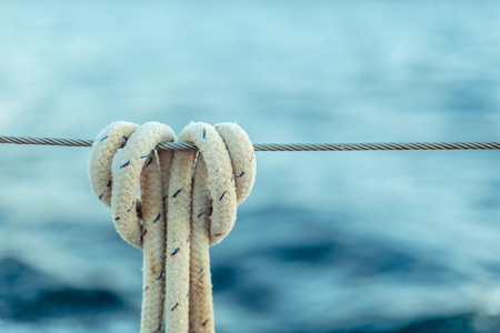 The rope knot on a steel cable on background of ocean. Stock Photo