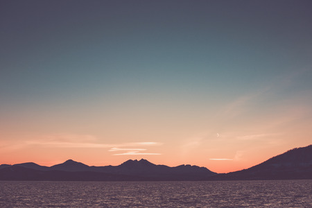 Beautiful pink sunset sky over the silhourtte of the mountains on the seaside. Stock Photo