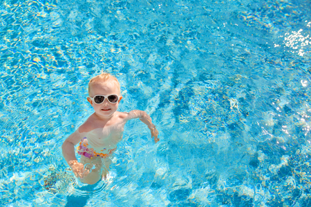 Little blonde girl swims in the pool with blue water. The view from the top. Place for text.