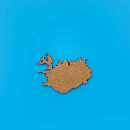 Wooden shape of map of Iceland isolated on blue background..
