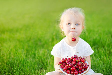 A little cute girl sitting on the grass in the garden with a plate of cherries on her knees and holding a berry in her teeth. Soft focus.