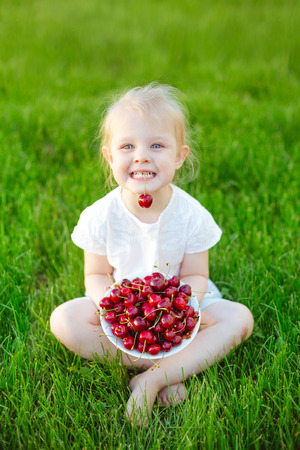 A cheerful baby girl sitting on the green grass in the garden with a plate of cherries on her knees and holding a berry in her teeth. Concept of vacation and childhood.
