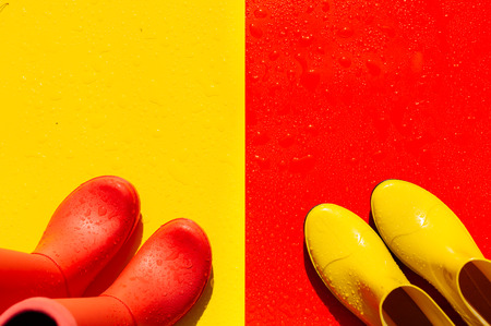 Red wet background with yellow gumboots and yellow background with red gumboots on it. The view from the top. The concept of