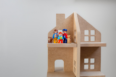 Three toy figures of family with pets - man, woman, kid, cat and dog in a wooden toy house. A symbol of a family in their own new home. 免版税图像