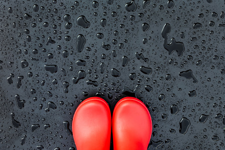 The edges of the red rubber boots are on a wet wet surface covered with raindrops. Copy space. Top view.