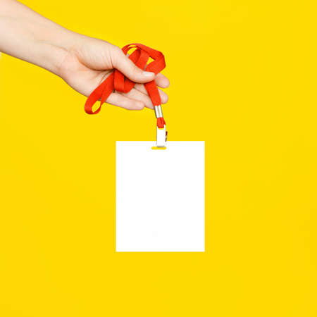 The womans hand holds a clean white badge on a red cord on a bright yellow background.