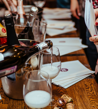 Moscow, Russia-March 30, 2019: wine tasting: on a wooden table there are silver buckets for cooling wines with bottles of champagne, there are brochures and glasses in which champagne is poured. 報道画像