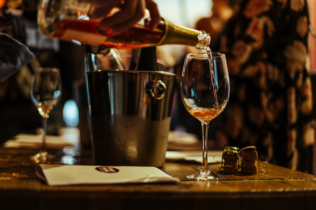 Moscow, Russia-March 30, 2019: wine Tasting: A glass of pink champagne is poured, and next to it on the tasting table are brochures, champagne corks and silver buckets in which the wines are cooled.