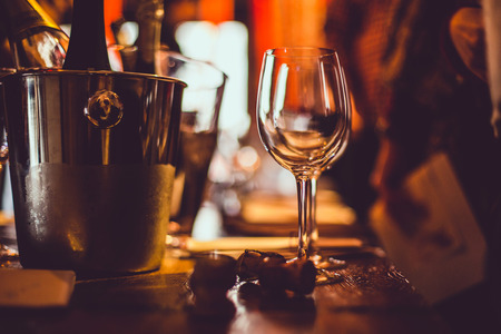 wine tasting: an empty glass stands on the tasting table next to brochures, champagne corks and silver buckets in which the wines are cooled.
