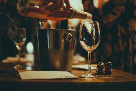 wine tasting: on a wooden table there are silver buckets for cooling wines with bottles of champagne, there are brochures and glasses in which champagne is poured. 写真素材