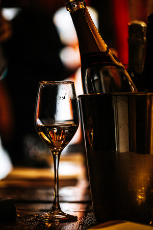 wine tasting: on a wooden table there is a silver bucket for cooling wines with open bottles of champagne and a glass of wine.