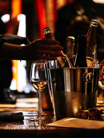 wine tasting: there is a glass of wine on a wooden table, and a silver bucket for cooling wines with open bottles of champagne, from which a bottle is taken out.
