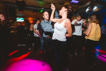 MOSCOW, RUSSIAN FEDERATION - OCTOBER 13, 2018: A middle-aged couple, a man and a woman, dance salsa among a crowd of dancing people in a nightclub Tiki bar. Long exposure, blurred motion. Archivio Fotografico - 137379117
