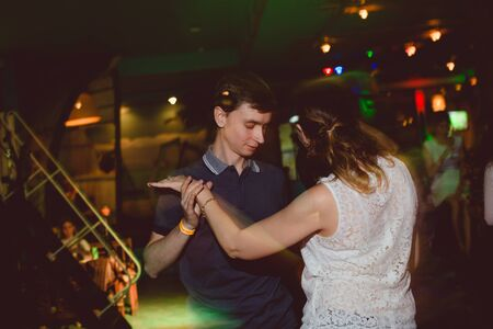 MOSCOW, RUSSIAN FEDERATION - OCTOBER 13, 2018: A middle-aged couple, a man and a woman, dance salsa among a crowd of dancing people in a nightclub Tiki bar. Long exposure, blurred motion. Archivio Fotografico - 137379123