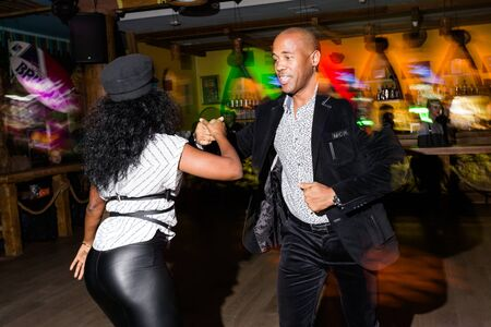 MOSCOW, RUSSIA - October, 13, 2018 - Black woman and man dansing Caribbean Salsa in night club. Long exposure. Archivio Fotografico - 137379124
