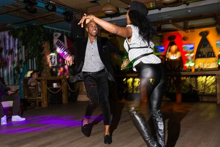 MOSCOW, RUSSIA - October, 13, 2018 - Black woman and man dansing Caribbean Salsa in night club. Long exposure. Archivio Fotografico - 137379126