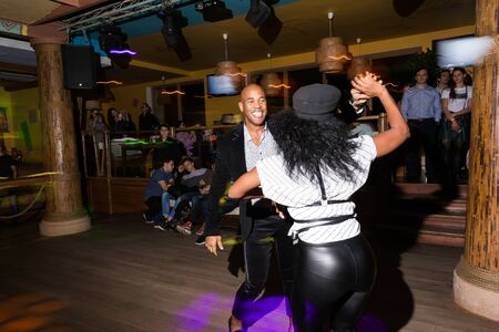 MOSCOW, RUSSIA - October, 13, 2018 - Black woman and man dansing Caribbean Salsa in night club. Long exposure. Archivio Fotografico - 137379128