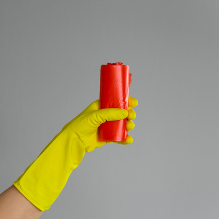 Hand in rubber glove holds colored garbage bag on neutral background. The concept of bright spring, spring cleaning. 免版税图像