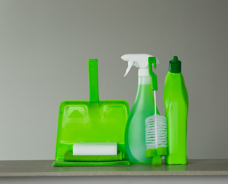 Green detergent bottle for toilet, spray bottle, brush, sponge, scoop and dust on grey background. Cleaning tools. Archivio Fotografico