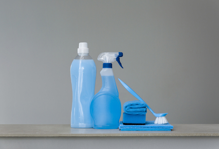 Cleaning blue set on grey background. Cleaning tools and products. Copy space.