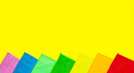 Colorful microfiber dust cloths lie on a bright yellow background. Set of housework equipment.