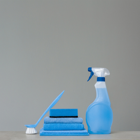 Cleaning blue spray bottle with plastic dispenser, sponge, scrubbing brush for dish and cloth for dust  on grey background. Cleaning tools. Copy space.