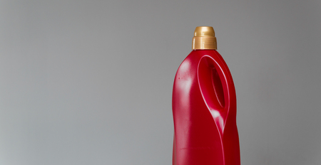 Red bottle of sanitary ware cleaner on grey background. Banque d'images