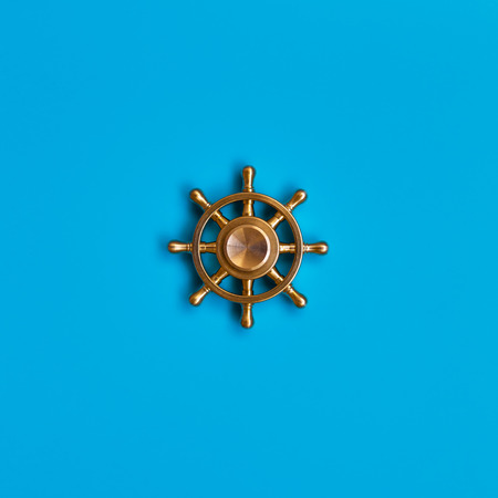 Ship's wheel on blue background. Symbol of management and leadership.