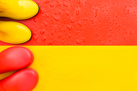 Red wet background with yellow rain boots and yellow background with red rain boots on it. The view from the top. The concept of