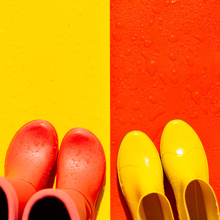 Red wet background with yellow rubber boots and yellow background with red boots on it. The view from the top. The concept of