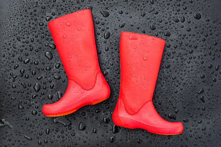 Trendy red rubber boots on black wet surface covered with raindrops. Top view, space for text.