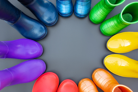 Colorful rubber boots of all colors of the rainbow-red, orange, yellow, green, blue, cyan and purple stand on the gray surface in a circle. Top view, space for text. Foto de archivo