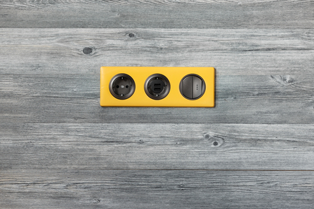 Triple bright yellow frame with power socket, usb ports and light key switch on grey wooden wall. Place for text.