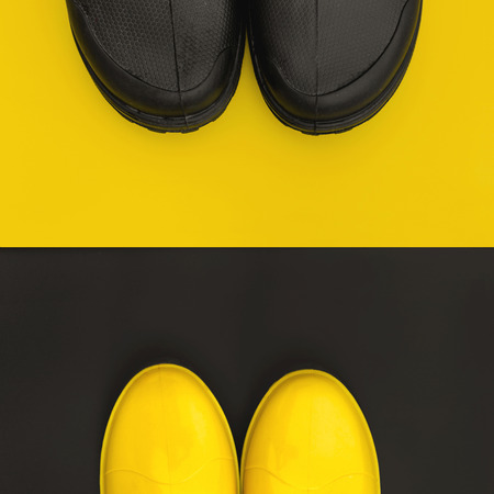 The front parts of the rain shoes are facing each other on the inversive backgrounds. Colorful and vivid concept of autumn Stock Photo